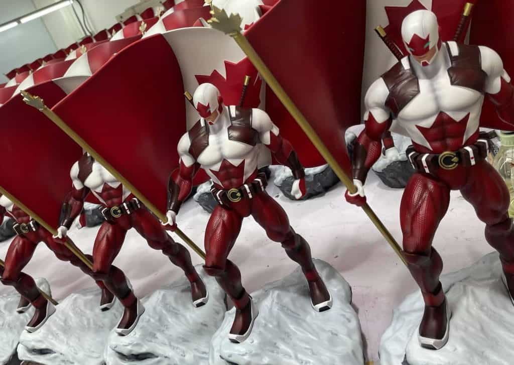 A row of Captain Canuck statues on a production table in 1/6 scale sculpted in polystone
